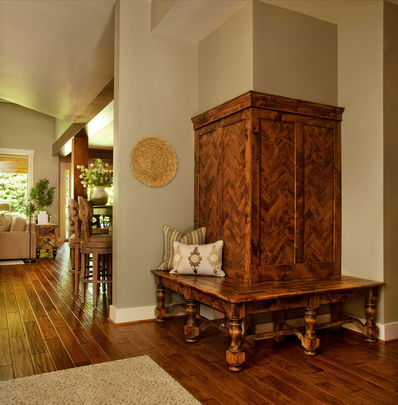 Over the rich natural hardwood flooring stands a variety of intricately carved wood furniture pieces, including this wraparound bench feature, built into a corner wall.