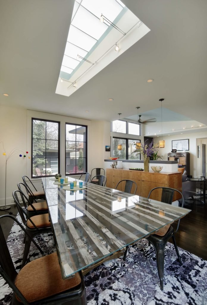 Dining area features a glass table framed with natural wood and paired by cushioned chairs over a shaggy rug. It also has a skylight with industrial lights.