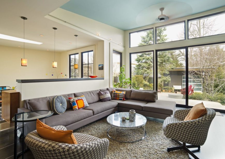 The living room stands luxuriating in sunlight via full height windows, with a pair of modern armchairs sharing an area rug with a lengthy contemporary sectional.