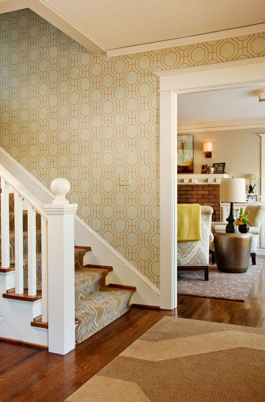 From the first moment a visitor steps in the home, they are greeted with a geometric pattern that echoes through the wallpaper, the entry rug, and in the more colorful carpet runner up the stairs. Dark hardwood floors run throughout the main floor, flowing from one space to the next. From this angle we can also see into the living room