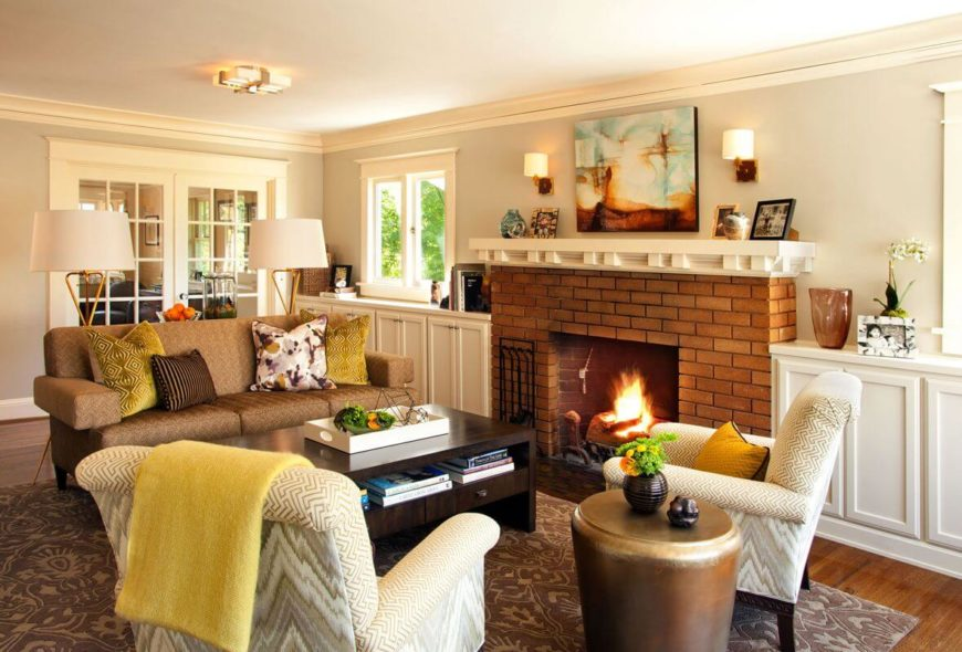 A view of the entirety of the living room, featuring a beautiful red brick fireplace and a patterned area rug. The dark wood coffee table includes drawers and a shelf below the table top. The built-ins run along the wall with the fireplace, and are ample storage and a perfect place to display photographs and other accents.