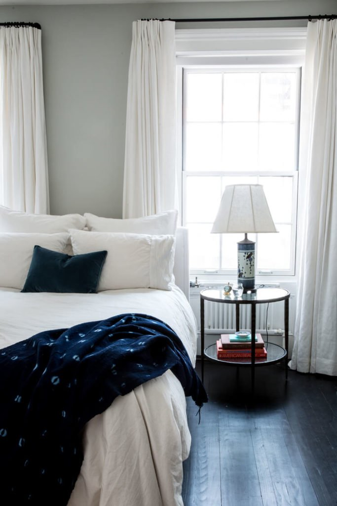 The bedroom continues the high contrast theme, with white sheets and drapes over the dark hardwood flooring. A simple two-tiered circular bedside table stands beneath the large window.