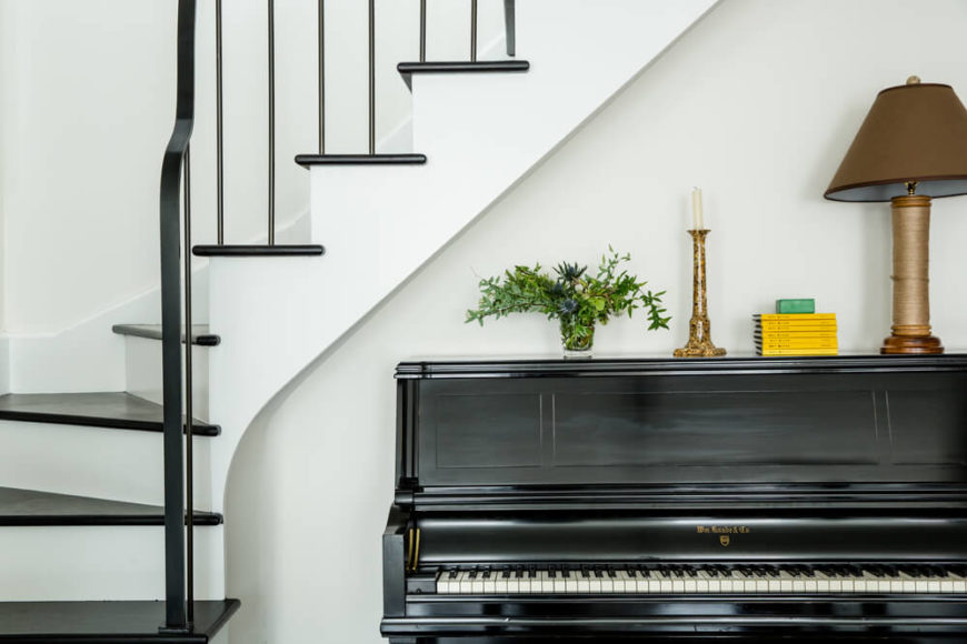 The foyer features an immaculate upright piano, set with arty pieces beneath the curved staircase.