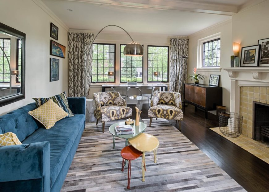 This more formal living room, centered on a large fireplace at right, sees a beguiling mixture of textures throughout. Striped area rug over rich hardwood flooring holds a lengthy blue sofa and pair of armchairs, plus a tri-colored array of coffee tables.