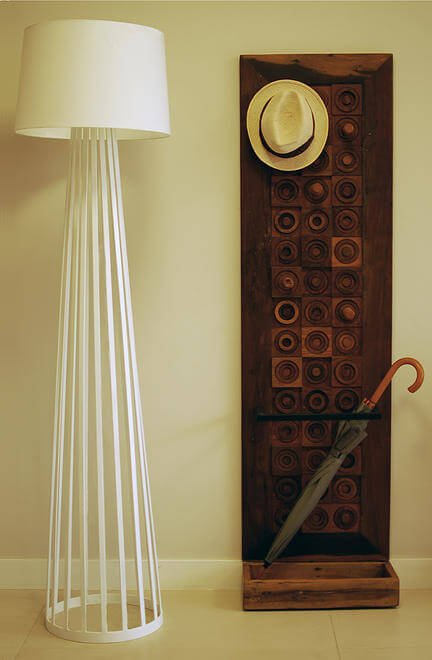Interesting details abound in the home, including this cage-frame floor lamp and carved wood hat rack and umbrella stand.