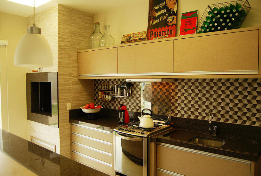 Geometric backsplash adds contrast and visual interest between thick slab countertop and floating minimalist cabinetry. A large marble wrapped fireplace stands mounted in the wall at left.