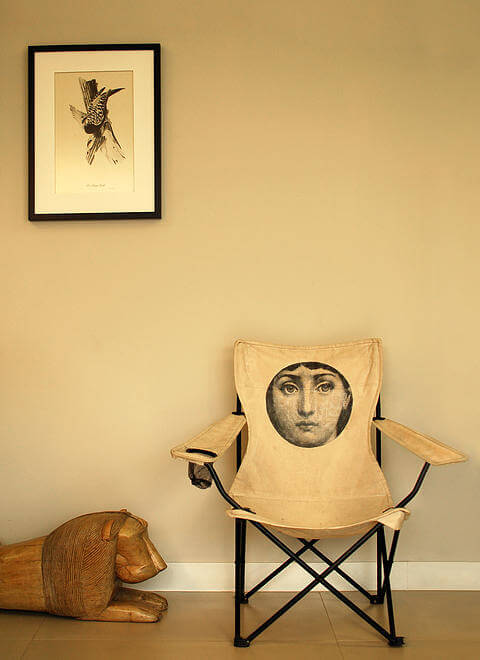 Similarly, next to the kitchen space stands this art-stamped folding chair and carved lion statue.