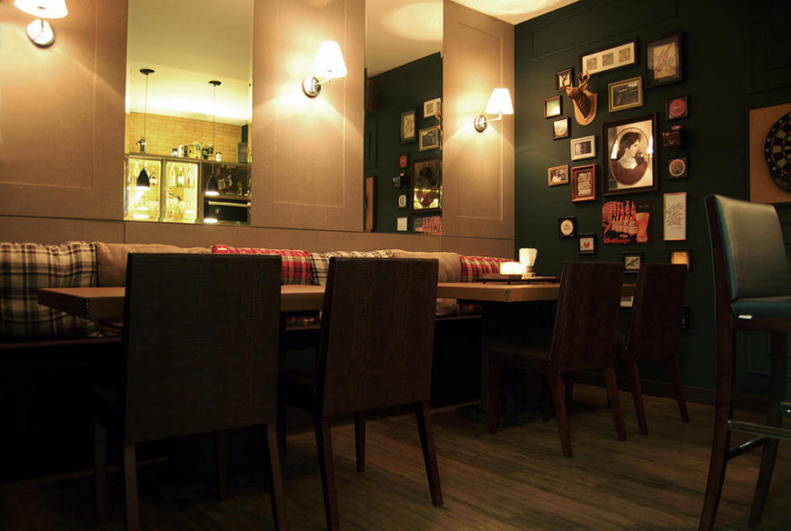 The pub room features a darker, more intimate ambiance, with sconces and dark painted walls creating atmosphere. Tables are set up like a proper pub.
