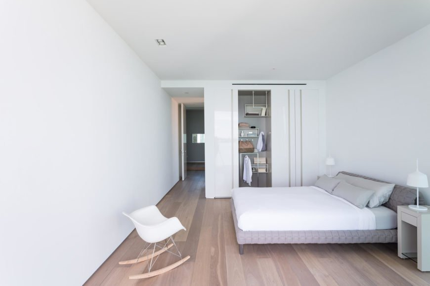 Bright white primary bedroom features gray tufted bed and accent chair over natural hardwood flooring.