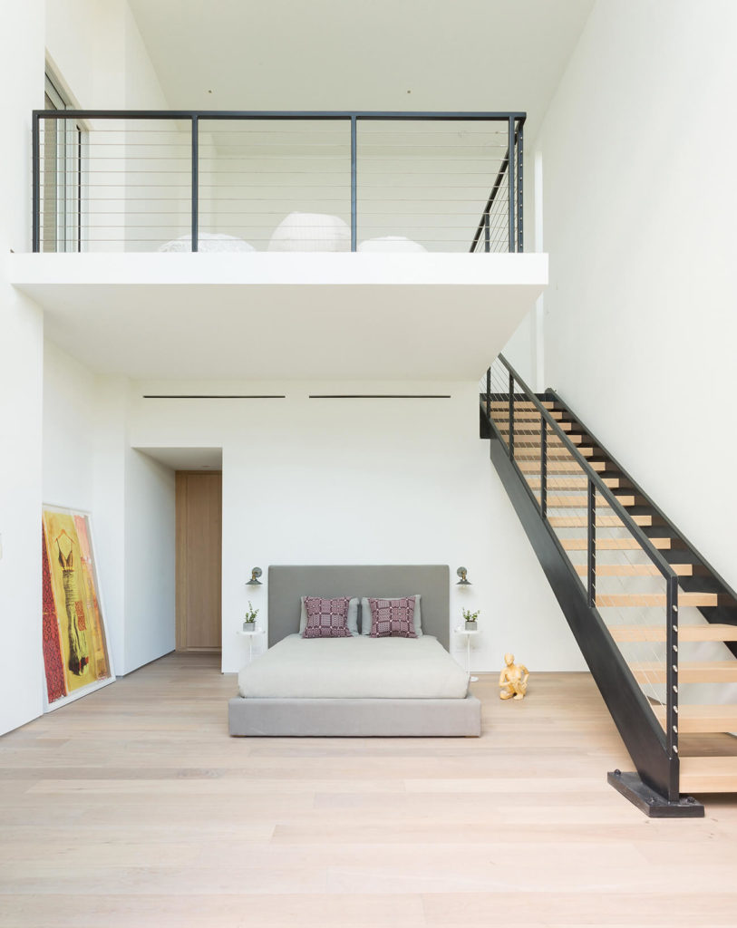 Spacious primary bedroom boasts a private loft area lined with an open riser staircase. Beneath it is the gray bed surrounded with art decor figurines.