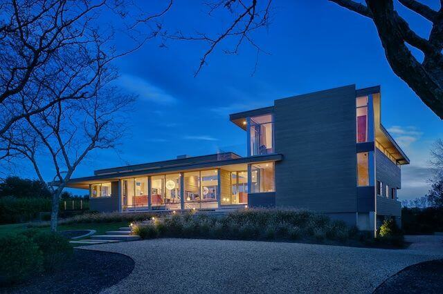 """The exterior of the home at night shows the extensive windows and the sturdy landscaping. The two-story section of the home contains all the bedrooms and bathrooms, while the kitchen, dining room, and living room are in the one-story """"pavilion."""""""