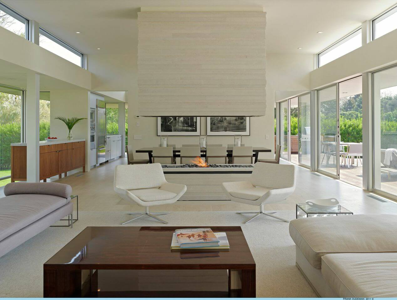 The modern-style living room is in a pristine white. The open-concept space is visually separated by a open-flame fireplace between the living room and dining room. Through the two archways behind the dining room is the kitchen.