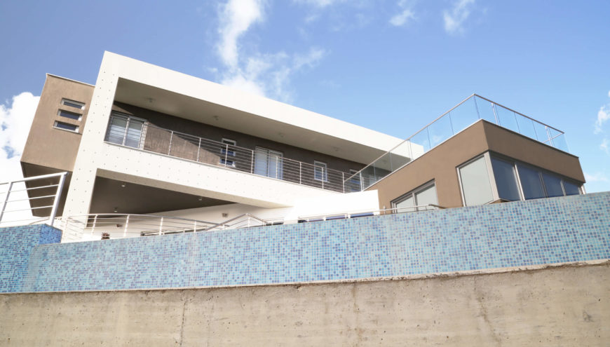 A blue tile wall encircles the home on this side, lending an aquatic edge to the sharply contemporary building. Thin railings abound, bracketing several expanses of balcony and patio.