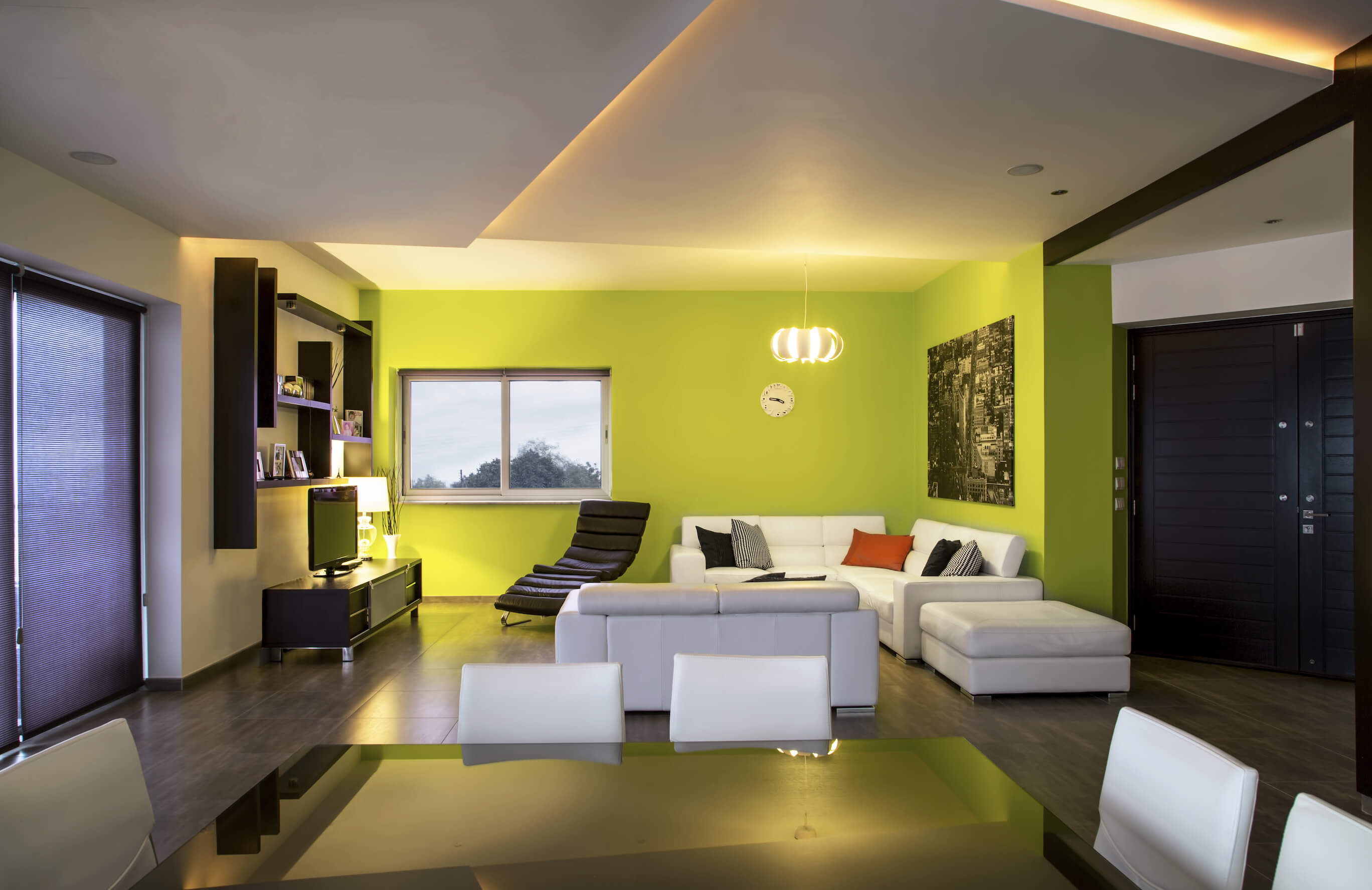 Viewed from across the deep black dining table, the living room stands hugged by a bold lime green set of walls, distinguishing a playful space from the rest of the home interior.