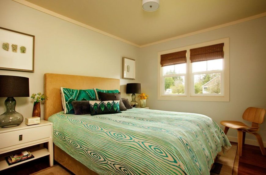 A second bedroom with a velour upholstered bed frame and green bedding. A small wooden chair sits near the foot of the bed.