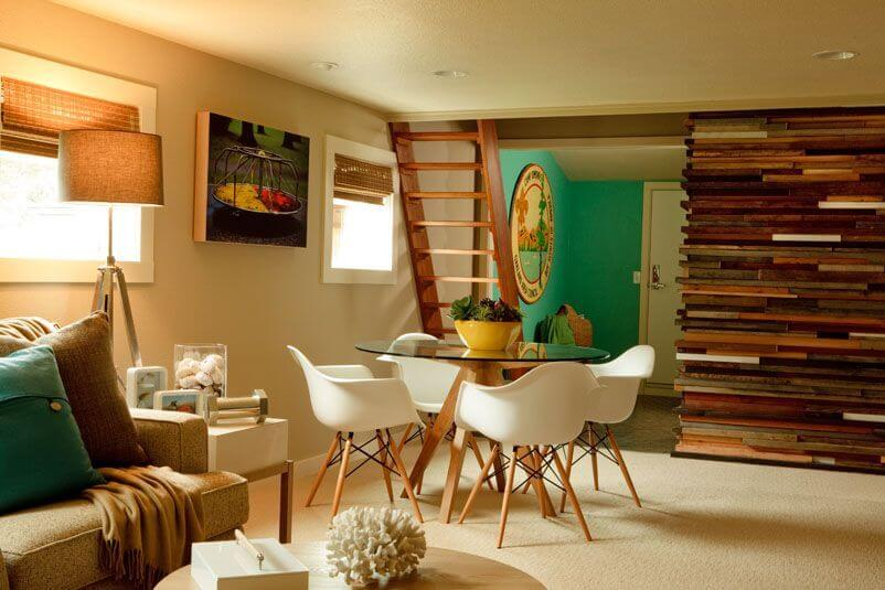Down a set of stairs is the family room, with a small circular table with white bucket chairs and a layered wood half-wall.
