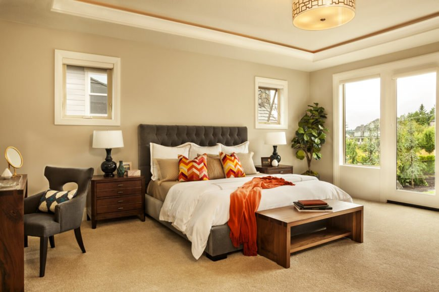 One of the two primary bedrooms with an upholstered bed frame, makeup table, and expansive windows.