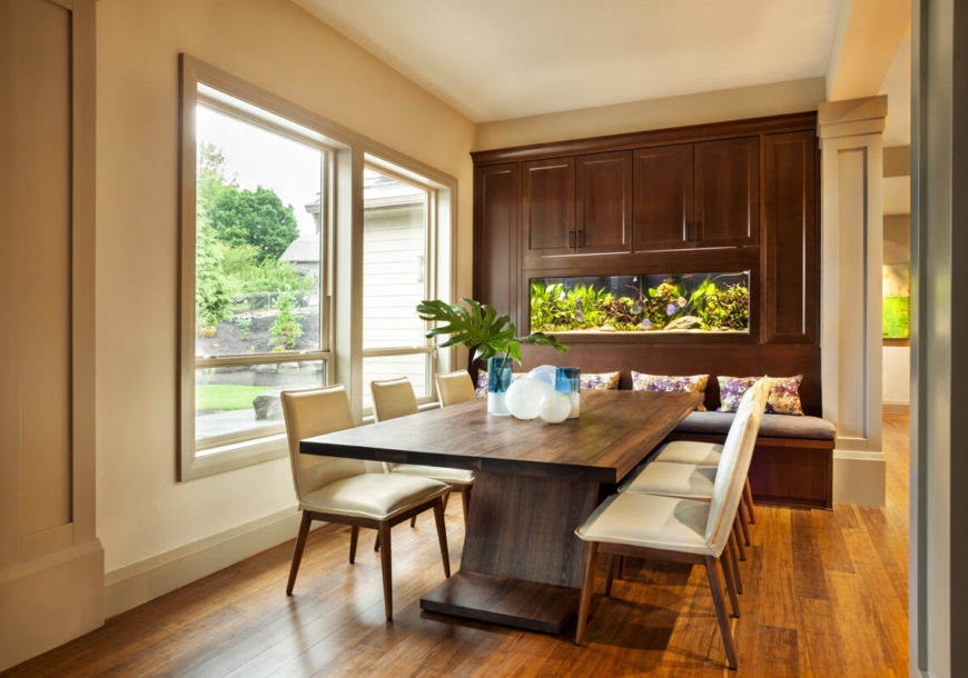 Another dining room with a built-in bench seat with a saltwater aquarium and cabinetry built above it.