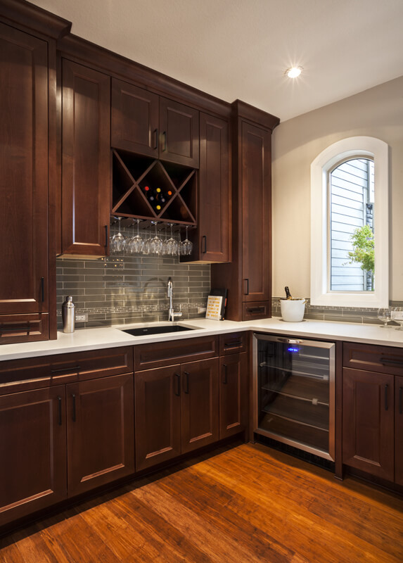 A close up of a section of a kitchen with open wine glass storage and a wine cooler.