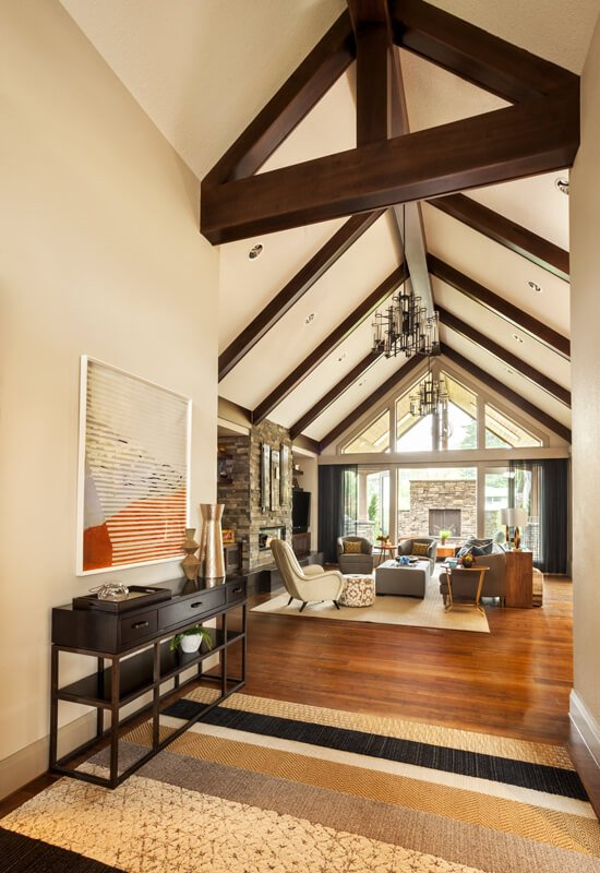 A look into the living room from the entryway, showing the exposed wood beams and enormous windows.