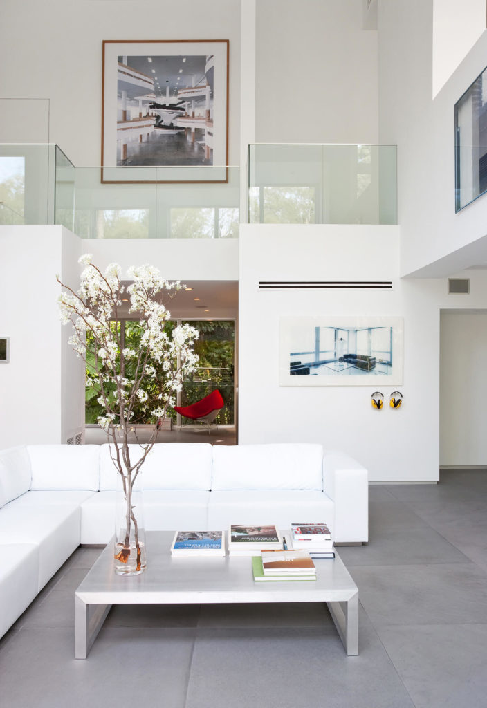 The open-plan, two-story living room centers on a large L-shaped sectional in bright white, hugging an immense metallic coffee table. Loft-style second floor space overlooks the room, with seamless glass walls for safety and clear visual space.