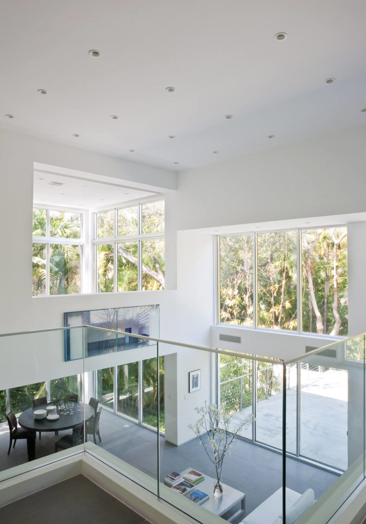Viewed from the upper floor through a low glass wall, we see the expansive nature of the open-plan design, bleeding into the outdoors through the exterior glass. Ceiling is dotted with precision embedded lighting for subtly powerful illumination.