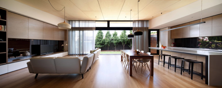 This panoramic view of the living room strikes a balance with its uniformity. The prolonged furniture--the L-shaped couch, the dining table and bar seating--maintain a prolonged effect, lending the an open feel to this room.