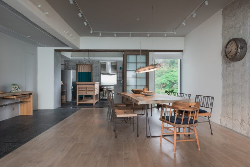 Looking into the dining area, the natural wood tones take the spotlight. The overhanging light, tabletop and wood floors add to the sense of depth within the room.