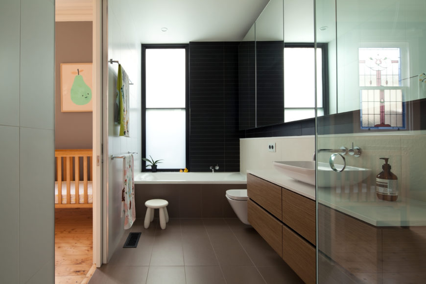 Facing the other direction of the bathroom, the true length of the sink becomes more marked, furthering the modern aesthetic of this bathroom. The far wall and window add contrast to the area with their licorice tones.