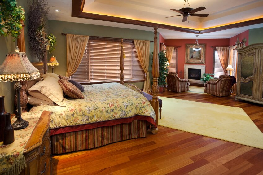A more eclectic bedroom, this design consists of green in the main sleeping area and transitions into bold red in the sitting nook. Floral bedding and accents mark this style as strictly English country.
