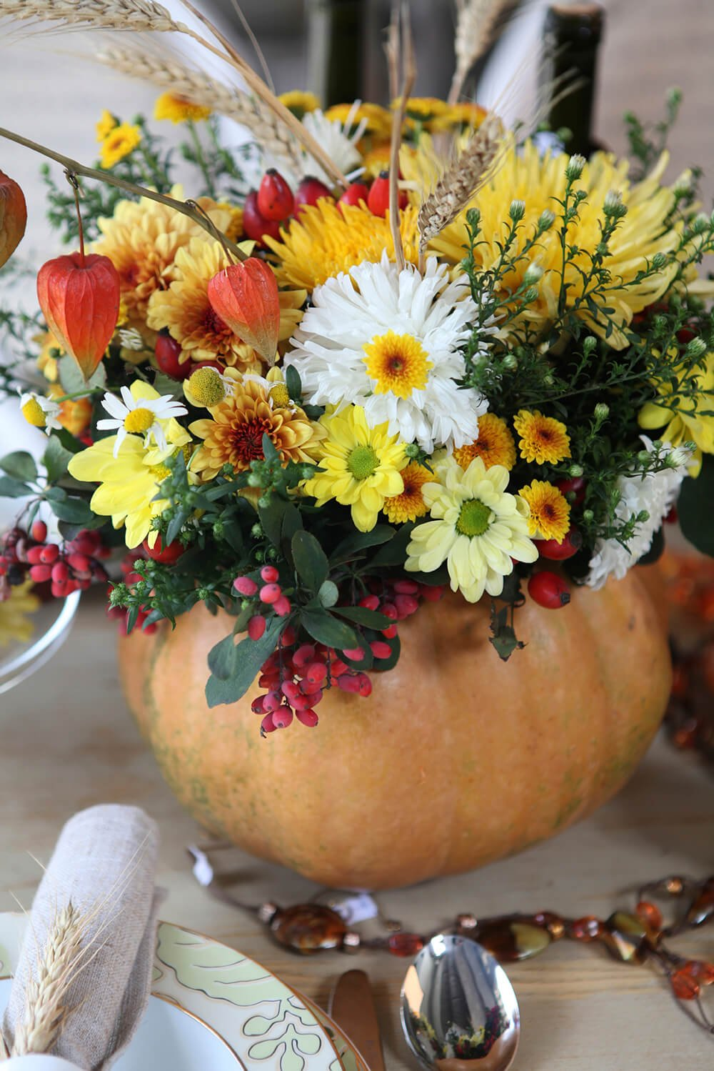 An autumn centerpiece full of daisies and holly berries, all resting neatly in a hollowed out gourd vase. The bouquet also includes sheaves of wheat, which match the accent on the napkin ring.