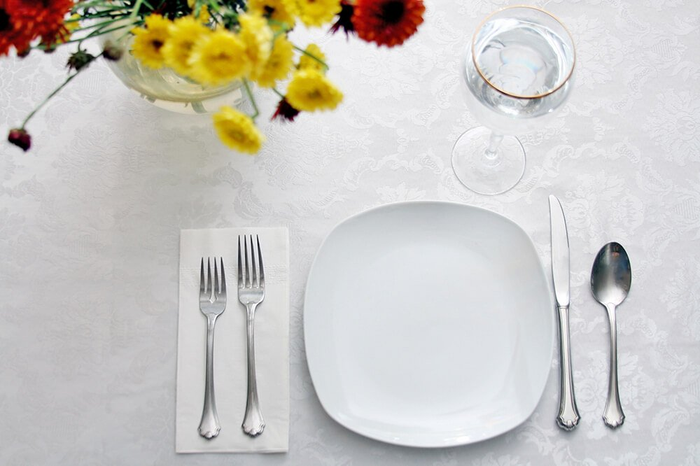 A simple, contemporary table setting with a gold-rimmed wine glass and a pretty floral arrangement.