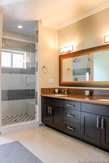 The full bathroom for the children is equally as simple, with a dark dual vanity and bronzy countertops. The shower stall is closed off by a glass door and contains the bathtub as well.