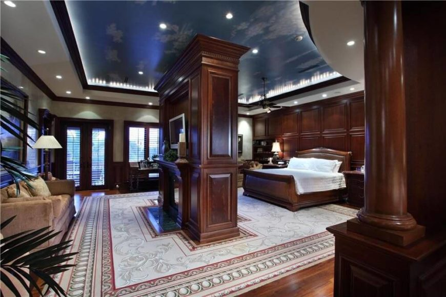 An absolutely stunning primary bedroom in polished hardwood. A center fireplace is dual-sided and can be enjoyed from the bed or from the sofa on the left.