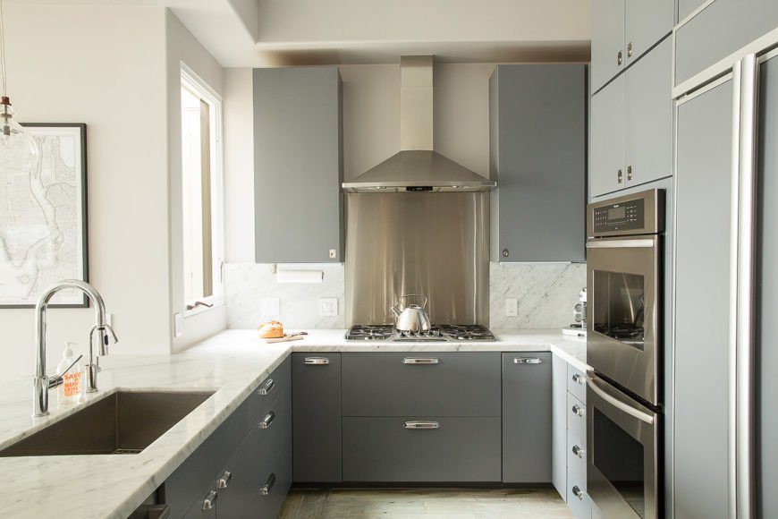 The stove is located in a small nook complete with a small window to shine light on the cooking range. The stainless steel backsplash perfectly complements the vent hood.