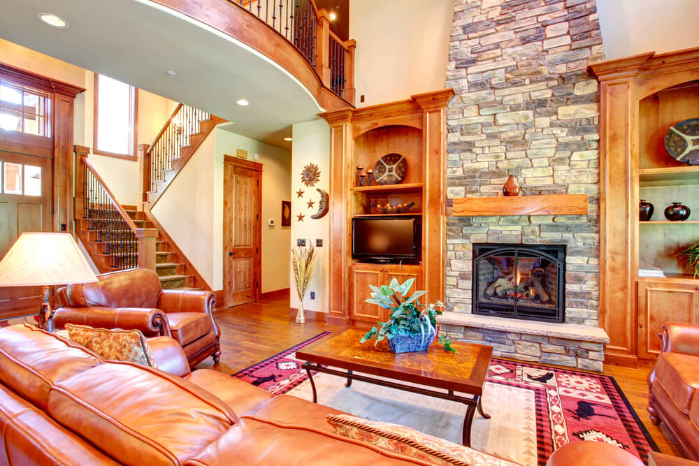 A traditional living room in light wood overlooked by the upstairs hallway. Built-ins on either side of the stone fireplace match the oak mantlepiece. The fireplace is gas, and enclosed in glass. The seating area in front is furnished in light brown leather.