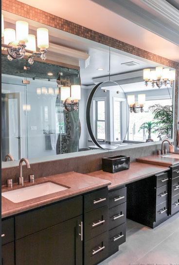 In the primary bedroom, some of the unique luxurious touches return. From this angle, we can see the dual vanities with a make-up table between the two. A circular mirror is layered on top of the seamless mirror.