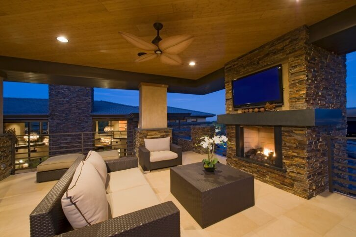 An outdoor living room surrounded by a balustrade. A large television is placed above the wooden mantle, above the glass-enclosed fireplace opening.