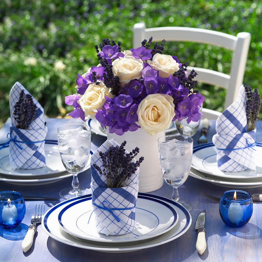A beautiful white ceramic vase is filled with bright purple flowers with large white roses and stalks of lavender.