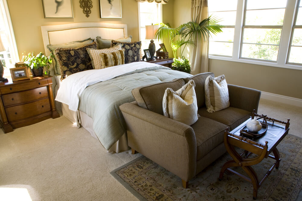 At the foot of the bed is a low-profile corduroy loveseat with a small tray table. This modestly sized bedroom makes the most of the expansive windows by not covering them with large furniture.
