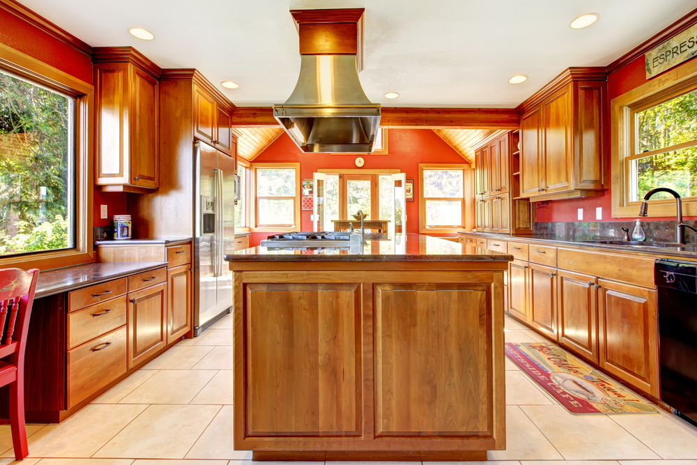This daring red kitchen features gorgeous natural wood cabinets and a sleek vent hood. A lot picture window above the bar works with other single-hung sash styled windows to illuminate the striking characteristics of this adventurous space.
