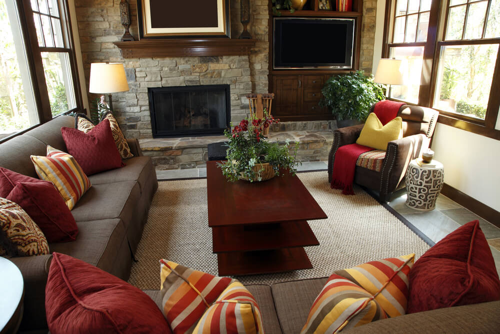 Windows line either side of this smaller contemporary living room. The fireplace is slightly off-center, allowing the television to be placed on the built-in beside it. The entire enclosure is in stone, with the wood as an accent.