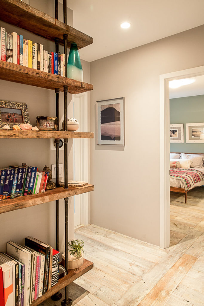 At the top of the stairs is a large reclaimed wood and industrial pipe bookcase filled with books and treasures from the homeowner's travels around the world.