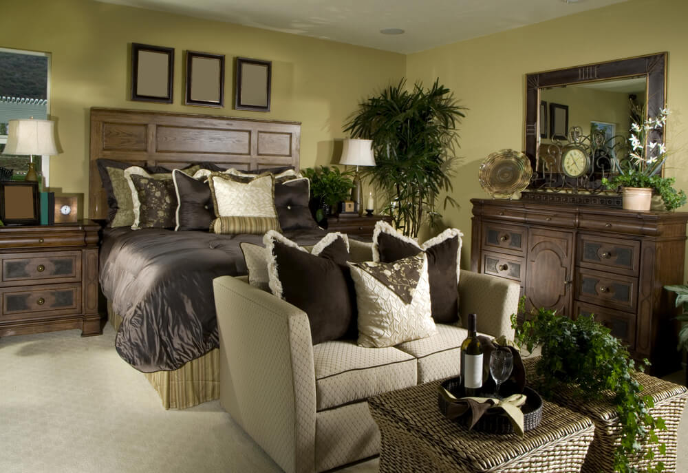 A smaller primary bedroom with a beige loveseat at the foot of the bed. A wicker coffee table holds a small tray with wine and wine glasses.
