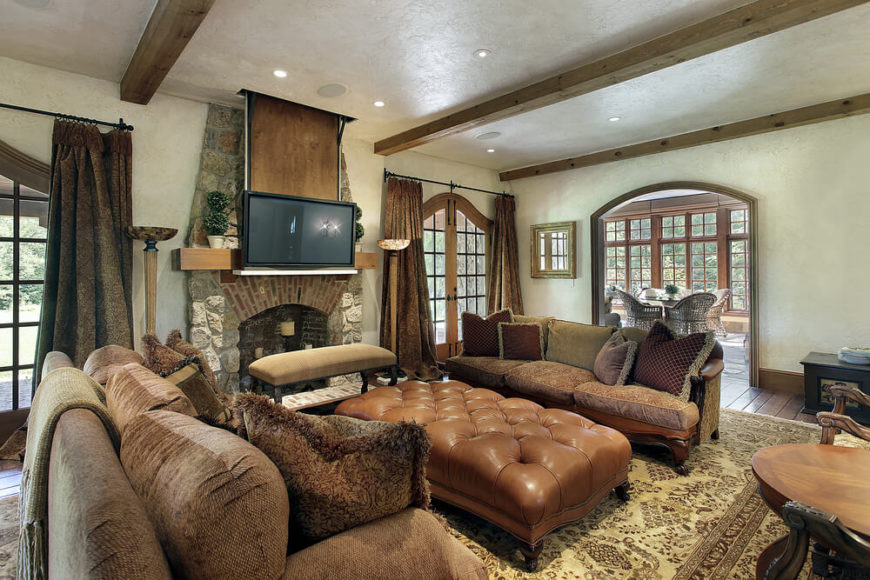 A comfortable living room with a set of large furniture. The ottoman in particular, is enormous. Another, more narrow bench sits directly in front of the stone fireplace. This design features pillar candles arranged on the inside of the fireplace instead of an actual fire.