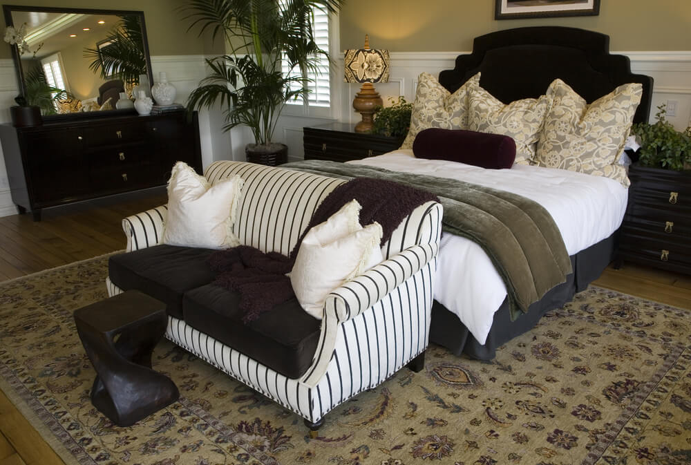 Like the above bedroom, this one places the loveseat at the foot of the bed with a small coffee table. The sofa is white with thin charcoal stripes.