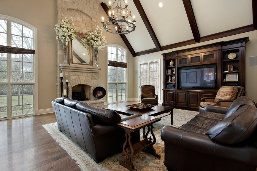 A large living room with a tall light stone fireplace with beautiful stonework. To the right is a massive dark wood entertainment center that matches the exposed beam ceilin