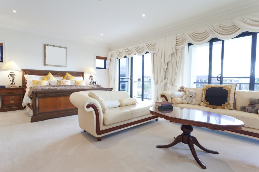 A light and bright primary bedroom with a large sofa and chaise lounge in cream with polished hardwood accents that match the tall table between the two. Sliding glass doors lead out onto a terrace.