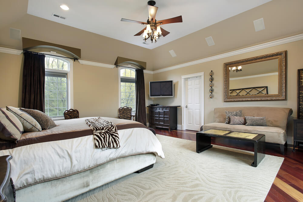A spacious primary bedroom with a deep tray ceiling and a large ceiling fan. Against the wall to the right of the door is a velour beige armless sofa with a small, slim coffee table in front of it.