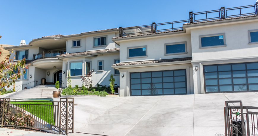 A wrought-iron gate surrounds the sprawling property of this enormous home. The gate leads directly up to either garage. Above the garages we can see a rooftop terrace.